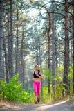 Junge Frau, die auf der Spur in der schönen wilden Kiefer Forest Active Lifestyle Concept läuft Raum für Text Stockfotografie