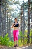 Junge Frau, die auf der Spur in der schönen wilden Kiefer Forest Active Lifestyle Concept läuft Raum für Text Stockfoto