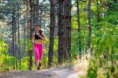 Junge Frau, die auf der Spur in schönen wilden Forest Active Lifestyle Concept läuft Raum für Text Lizenzfreie Stockfotos