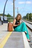Junge Frau, die auf der Station und dem Ablesen sitzt Lizenzfreie Stockbilder