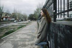 Junge Frau, die auf der Stra?e in einer braunen Wolljacke aufwirft stockfotografie