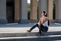 Junge Frau, die auf der Treppe sitzt und Musik hört Stockfotos
