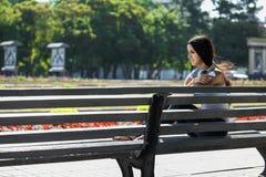Junge Frau, die auf der Treppe sitzt und Musik hört Stockfotografie