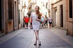 Junge Frau, die auf die Europa-Straße im weißen Kleid geht stockfoto