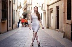 Junge Frau, die auf die Europa-Straße im weißen Kleid geht stockbilder