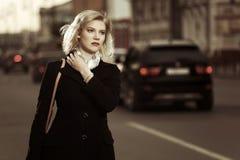 Blonde Frau, die auf die Stadtstraße geht Lizenzfreie Stockfotos