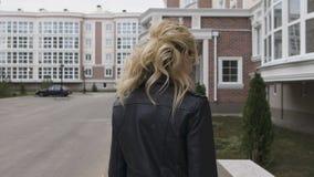 Junge Frau, die auf die Straße geht Blonde Drehungen, die Anstarren mit dem Zuschauer flirten Schwarze Lederjacke stock video