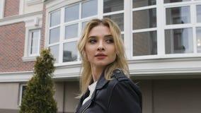 Junge Frau, die auf die Straße geht Blonde Drehungen, die Anstarren mit dem Zuschauer flirten Schwarze Lederjacke stock video footage