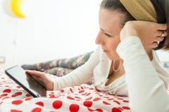 Junge Frau, die auf digitaler Tablette oder eBook Gerät schaut stockfotografie