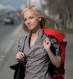 Junge Frau, die auf eine Stadtstraße geht Stockbild