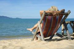 Junge Frau, die auf einem Aufenthaltsraum gegen das Meer sitzt stockbild