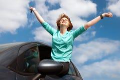 Junge Frau, die auf einem Autofenster sitzt und einen Schlüssel hält Stockfotografie