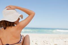 Junge Frau, die auf einem Badetuch beim Anhalten ihres Hutes sitzt Stockfotos
