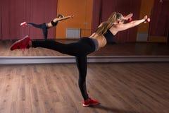 Junge Frau, die auf einem Bein im Studio balanciert Stockfotos