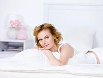 Junge Frau, die auf einem Bett sich entspannt Lizenzfreies Stockbild