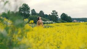 Junge Frau, die auf einem Blumengebiet geht Schönes Landschaftssommer-Blumenfeld stockfotos
