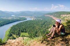 Junge Frau, die auf einem Felsen über dem Fluss sitzt lizenzfreie stockbilder