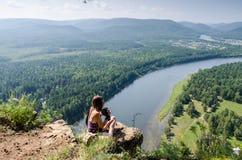 Junge Frau, die auf einem Felsen über dem Fluss sitzt lizenzfreies stockfoto