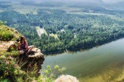 Junge Frau, die auf einem Felsen über dem Fluss sitzt Stockbild