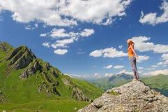 Junge Frau, die auf einem Felsen steht Lizenzfreies Stockfoto