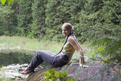 Junge Frau, die auf einem Felsen vor Tannenbäumen und einem Tarn steigt Stockbild