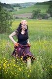 Junge Frau, die auf einem Gebiet der Blumen geht Lizenzfreie Stockfotografie