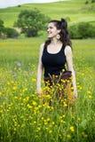 Junge Frau, die auf einem Gebiet der Blumen lächelt Lizenzfreies Stockfoto