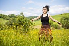 Junge Frau, die auf einem Gebiet der Blumen springt Stockfotografie