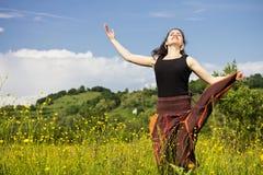 Junge Frau, die auf einem Gebiet der Blumen springt Stockbilder