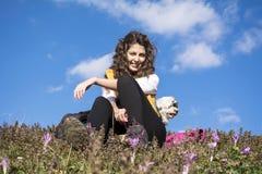 Junge Frau, die auf einem Gebiet von Blumen mit ihrem weißen Hund im Freien sitzt Stockbild