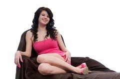 Junge Frau, die auf einem goldenen Stuhl aufwirft Stockbilder