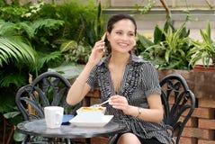 Junge Frau, die auf einem Handy über dem Mittagessen spricht Stockbilder