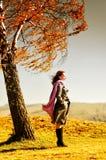 Junge Frau, die auf einem Herbsthügel steht lizenzfreies stockfoto