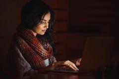 Junge Frau, die auf einem Laptop schreibt stockfotografie