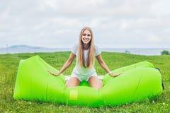Junge Frau, die auf einem Luftsofa im Park stillsteht Stockfoto
