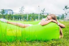 Junge Frau, die auf einem Luftsofa im Park stillsteht Lizenzfreies Stockfoto