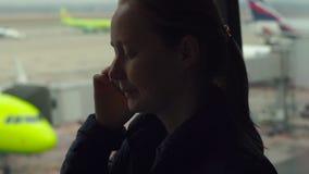 Junge Frau, die auf einem Mobiltelefon vor einem großen Fenster an einem Flughafen spricht stock video