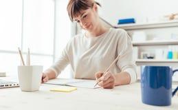 Junge Frau, die auf einem Notizbuch skizziert Stockbild