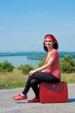 Junge Frau, die auf einem roten Koffer sitzt Stockbild
