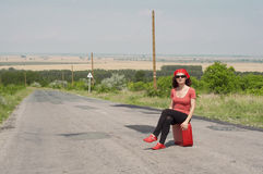 Junge Frau, die auf einem roten Koffer sitzt Stockbilder