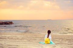 Junge Frau, die auf einem sandigen Strand betrachtet Meer und Sonnenuntergang sitzt Lizenzfreie Stockfotografie