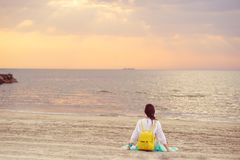 Junge Frau, die auf einem sandigen Strand betrachtet Meer und Sonnenuntergang sitzt Stockfotos