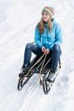 Junge Frau, die auf einem Schlitten im Schnee sitzt stockfotos