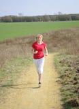Junge Frau, die auf einem Schotterweg rüttelt Lizenzfreie Stockfotos