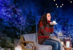 Junge Frau, die auf einem Schwingen mit einer Decke unter dem flashlig sitzt Lizenzfreies Stockfoto