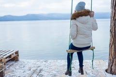 junge Frau, die auf einem Schwingen an einem See sitzt stockfoto