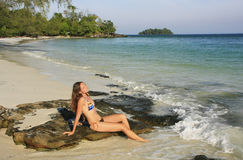 Junge Frau, die auf einem Strand von KOH Rong Insel, Kambodscha sitzt Stockfotografie