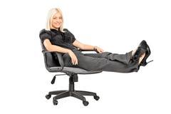 Junge Frau, die auf einem Stuhl mit ihren Fahrwerkbeinen oben sitzt stockfotografie