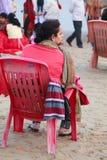 Junge Frau, die auf einem Stuhl am Seestrand sitzt lizenzfreie stockfotografie