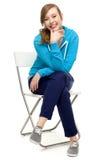 Junge Frau, die auf einem Stuhl sitzt Lizenzfreies Stockfoto